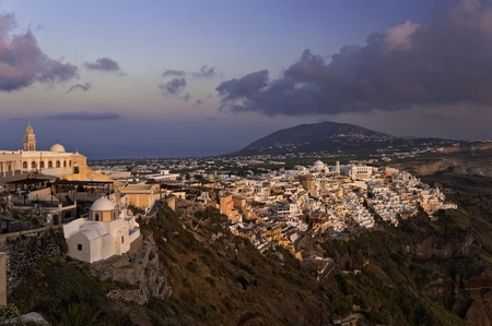 thira: Sunset in Thira town with white and orange buildings on the rock Stock Photo