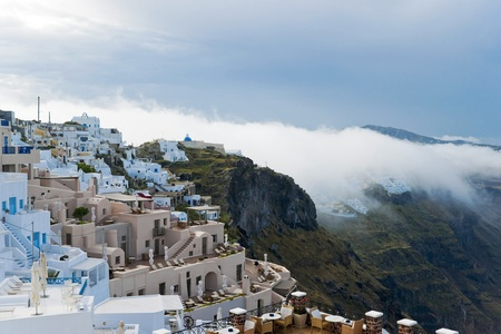 Santorini buildings and cliffs in the morning fog photo