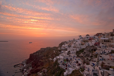 Santorini sunset in Ia village with the ship coming to the island photo
