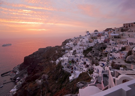 sunbeds: Santorini sunset in Ia village with the ship coming to the island Stock Photo