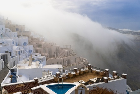 Santorini buildings and cliffs in the morning fog