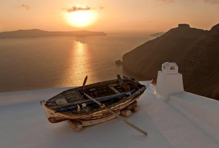 Coucher de soleil � l'�le de Santorin avec le bateau comme une d�coration de la maison toit