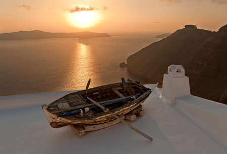 Sunset in Santorini island with the boat as a decoration of the house roof Stock Photo