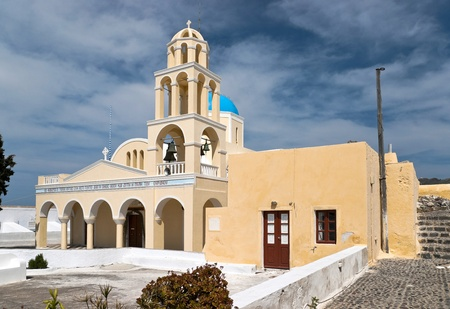 Yellow greek church with arcade porticos and belltower photo