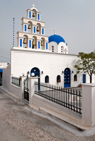 White Greek church with belltower and the yard photo
