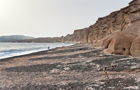 Vlichada beach in Santorini with volcanic walls and a pair of old shoes in front photo