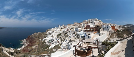ia: Santorini Ia panorama with typical architecture houses and greek flag