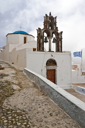 clody sky: Old Greek church with belltower and greek flag