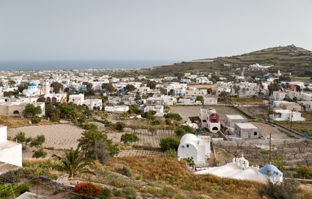 Santorini village with buildings and vegetable gardens on sea background photo