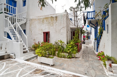 Mykonos street and yard with external stairs of the houses and colorful balconies photo
