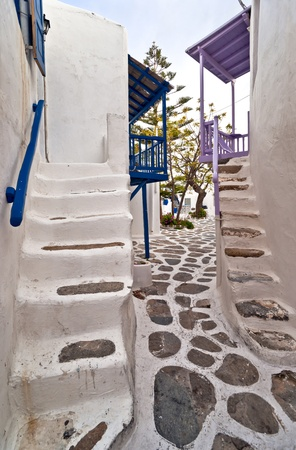 Mykonos street with external stairs of the houses and colourful balconies photo