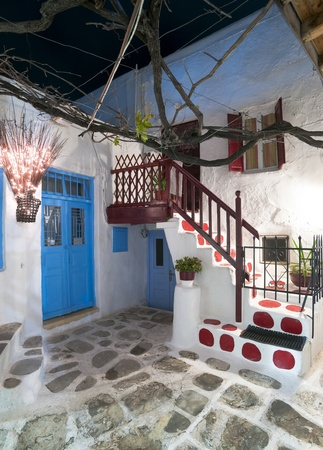 Mykonos cosy house yard with external colourful stair and balcony at night