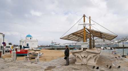Empty Mykonos town fish market out of season with a senior citizen looking at camera