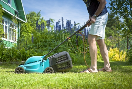 Man mowing the lawn in the yard of a country house Stock Photo