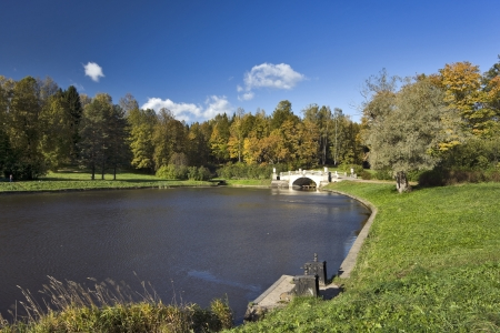 Classical stone bridge over river in the autumn park photo