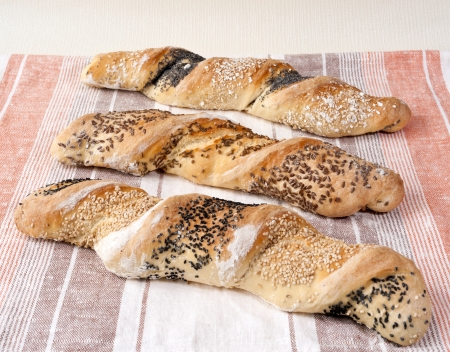 dishcloth: Three twisted loaves of white bread with seeds on the dish-cloth