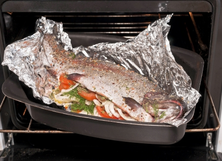 cookie sheet: Rainbow trout with vegetable in foil on the metal cookie sheet in the open oven