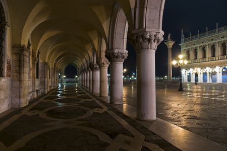 theodor: Doges Palace arcade with S Theodor column and Biblioteca Marciana view in winter night
