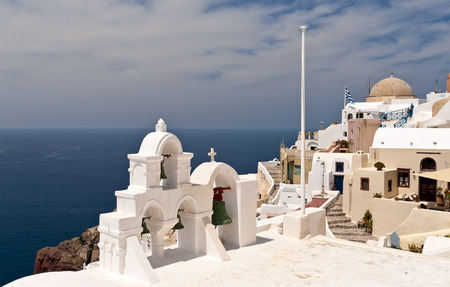eruptive: Greek church bell-tower and buildings over Aegean sea Stock Photo