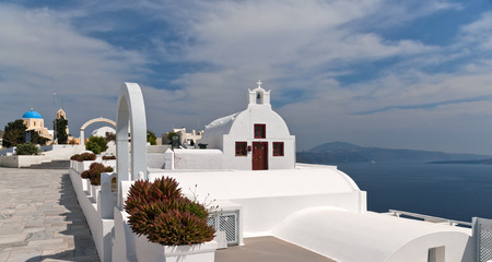 White and yellow Greek churches next to caldera in Santorini island photo