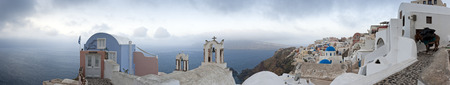 Santorini morning panorama with houses, churches and a donkey at the right side photo