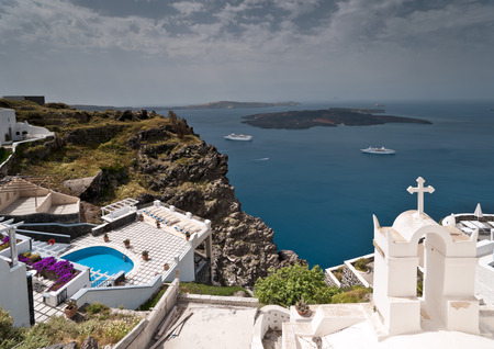 Santorini caldera view with white passenger ferries and church in front photo
