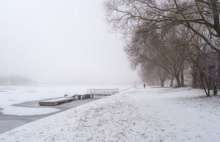 distantly: Winter mist in the park next to the river with pier and lonely mans figure distantly Stock Photo