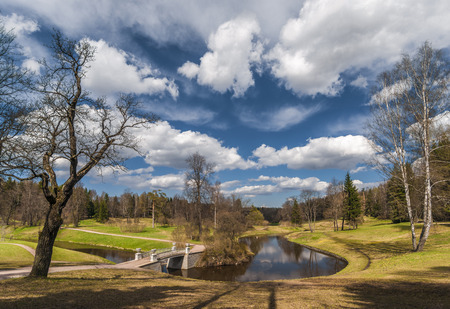 Classical bridge over river and beautiful cloudy sky in awakening spring park