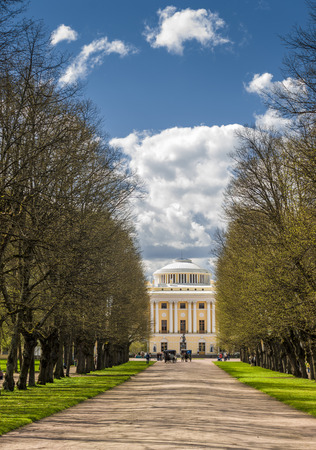 Spring wide alley to classical style palace with people, horses, carts in front, Pavlovsk, Russia