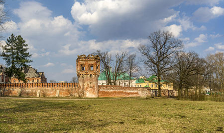 Early Spring in the park with ruined red brick wall, yellow last years grass and awakening trees, Pushkin, Russia Stock Photo