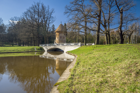 Tower with conic roof view with river and bridge in beautiful spring park Stock Photo