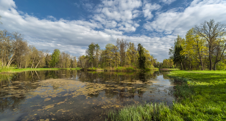 Early spring park and pond panorama with picturesque cloudy sky
