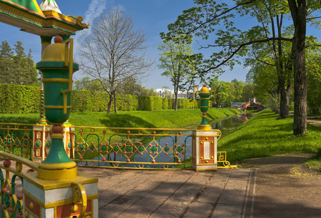 Park landscape with river and multicolored bridge fence Stock Photo