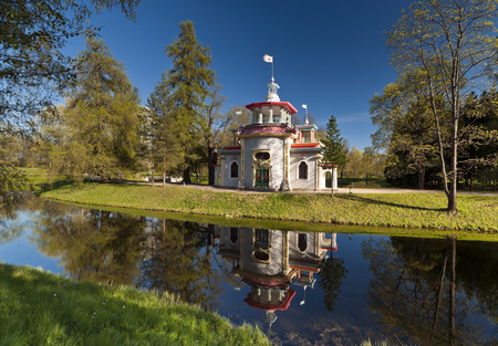 Chinese style pavilion with its water reflection in spring park Stock Photo