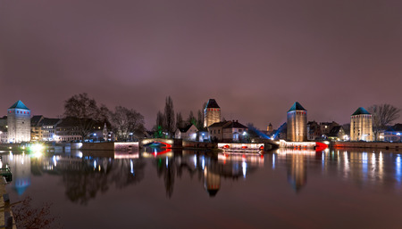 Towers and bridges panorama with illumination at night, Ponts Couverts, Strasbourg, France