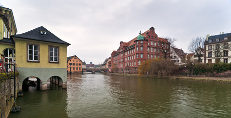 River Ile in Strasbourg with buildings and quay in cold cloudy day Stock Photo
