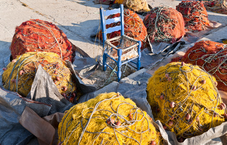 Red and yellow fishing nets and blue chair in the center on the pier, Skopelos island; Sporades; Greece Stock Photo