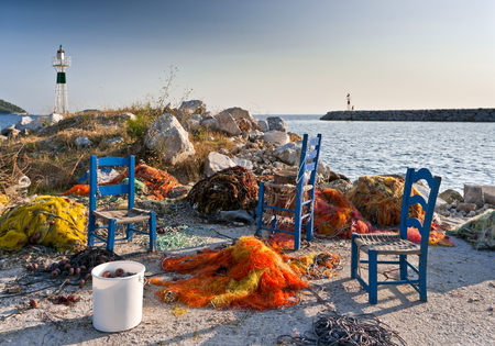 Multicolored fishing nets, blue chairs on the pier, and small lighthouses next to the sea, Skopelos island; Sporades; Greece