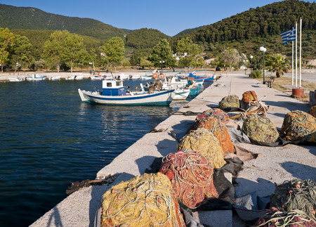 Multicolored fishing nets on the pier and fish boats in small harbour, Skopelos island; Sporades; Greece