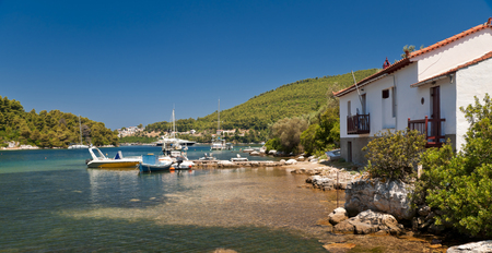 Calm sea bay with yachts, boats and houses on Skopelos island in summer day