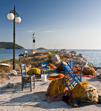Multicolored fishing nets and blue chairs on the pier,  street lantern and small lighthouse next to the sea, Skopelos island; Sporades; Greece