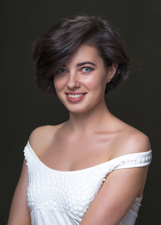 Young pretty brunette girl in white top is looking to the camera and smiling, dark background