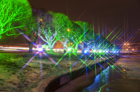 New Year illumination on and between trees next to frozen river and street, star filter Stock Photo