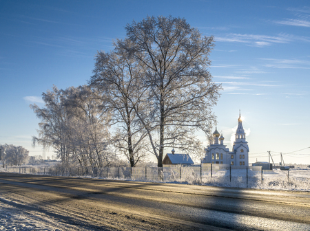Orthodox white church with golden cupola and bell-tower next to the country road in sunny winter day Stock Photo