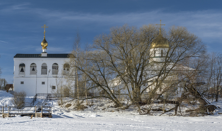Orthodox white church and Bell-tower with golden cupolas next to river under snow in sunny winter day