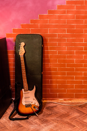 Electric rock guitar with case on background of stylized brick wall