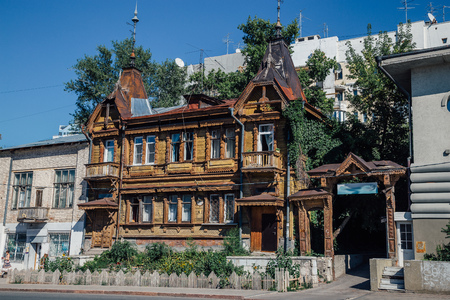 Old wooden Mansion  with wood carvings next to modern buildings. Samara, Russia