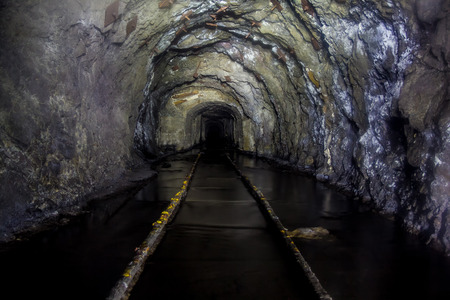 Flooded tunnel of an old abandoned coal mine with rusty remnants of railroad