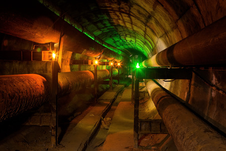 subterranean: Dirty tunnel of heating duct with rusty pipeline illuminated by candles and green lantern Stock Photo