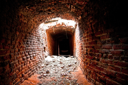 An abandoned and collapsed historic underground passage made of red brick